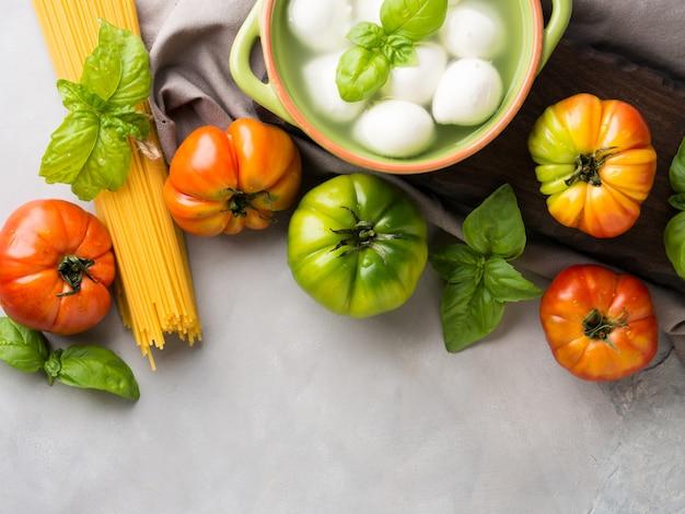Włoskiego jedzenia pomidorowa mozzarella wciąż życie na szarym nieociosanym tle. tradycyjne produkty