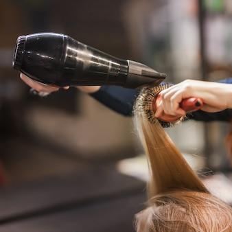 Włosy blond zaczesane i wysuszone