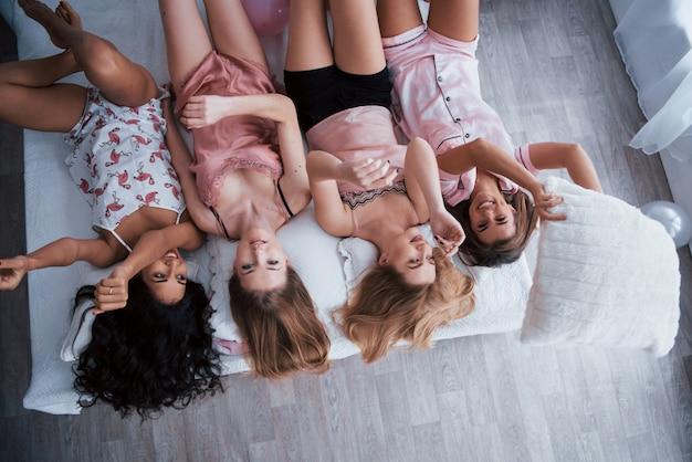 Włosy i ręce do góry. odwrócony portret uroczych dziewczyn leżących na łóżku w nocnej bielizny. widok z góry