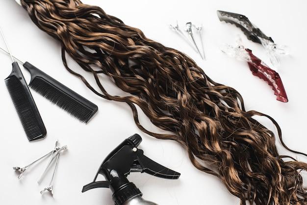 Włosy kanekalon na białej powierzchni z grzebieniami i akcesoriami do włosów