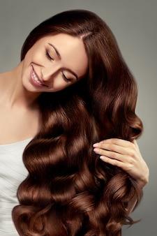 Włosy. piękna dziewczyna z długimi falowanymi i lśniącymi włosami. brunetka kobieta z wspaniałą kręconą fryzurą. pielęgnacja włosów. zdrowe długie włosy. model piękna kobieta. brązowe włosy.