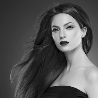 Włosy piękna kobieta długo bruette gładkie piękny manicure paznokcie model czerwona szminka brązowym tle wieczór makijaż portret. strzał studio. szary. monochromia. czarny i biały.