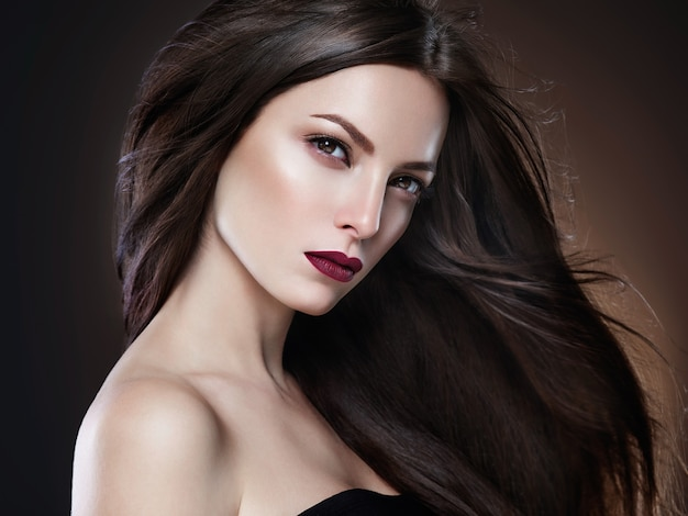 Włosy piękna kobieta długo bruette gładkie piękny manicure paznokcie model czerwona szminka brązowym tle wieczór makijaż portret. strzał studio.