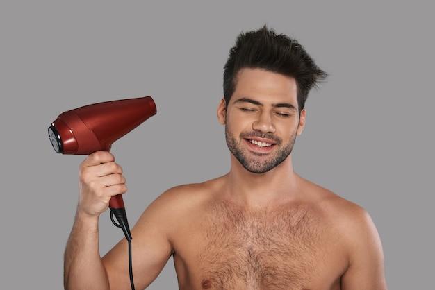 Włosy są ważną częścią jego wyglądu. przystojny młody mężczyzna suszy włosy i uśmiecha się stojąc na szarym tle