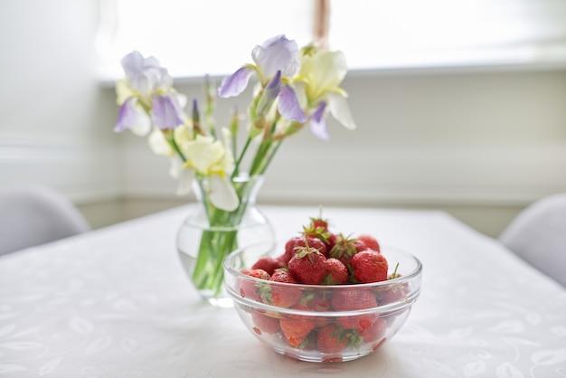 Wnętrza domowej jadalni, stół z białym obrusem, wiosenno-letni bukiet irysów w wazonie, miska z dojrzałymi truskawkami