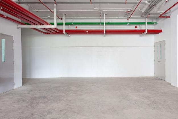 Wnętrza garażu parkingowego budynek przemysłowy hydrant z wężami wodnymi w budownictwie przemysłowym puste miejsce na tle przemysłu.