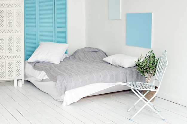 Wnętrze białego loftu w stylu skandynawskim. przytulna część mieszkania w stylu północnym, sypialnia z białą drewnianą podłogą, metalowym krzesłem i drzewem oliwnym. koncepcja makeover pokoju, wolne miejsce na tekst.