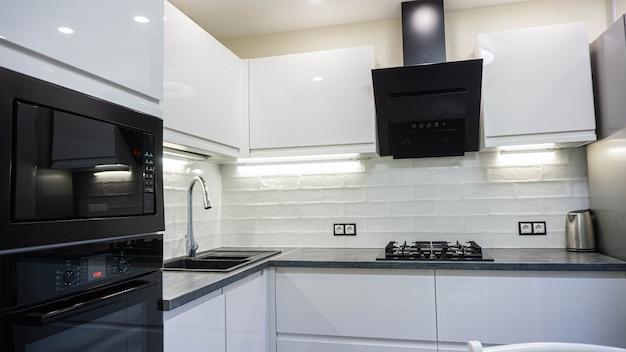 Wnętrze białych mebli kompaktowej kuchni błyszczącej szafki z wbudowanym sprzętem agd