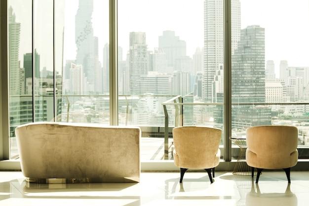 Wnętrze budynku z siedzeniami, z których widać widok na duże miasto