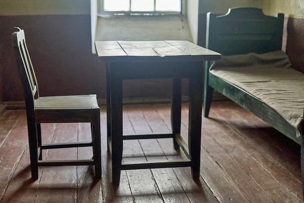 Wnętrze celi więziennej z drewnianymi meblami i światłem z okna. stara cela więzienna