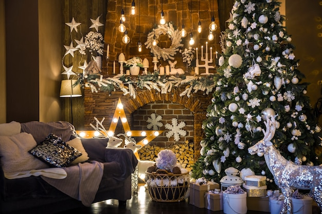 Wnętrze ciemnego pokoju z drzewem noworocznym ozdobionym prezentami i sztucznym kominkiem
