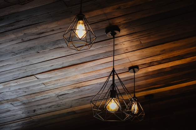 Wnętrze domu w stylu loftu i rustykalnym. pięknego rocznika luksusowej żarówki wiszący wystrój jarzy się w zmroku. styl retro efekt filtra. połączenie historii i nowoczesności.