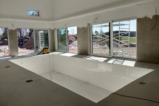 Wnętrze domu z dużym basenem w trakcie prac remontowych.