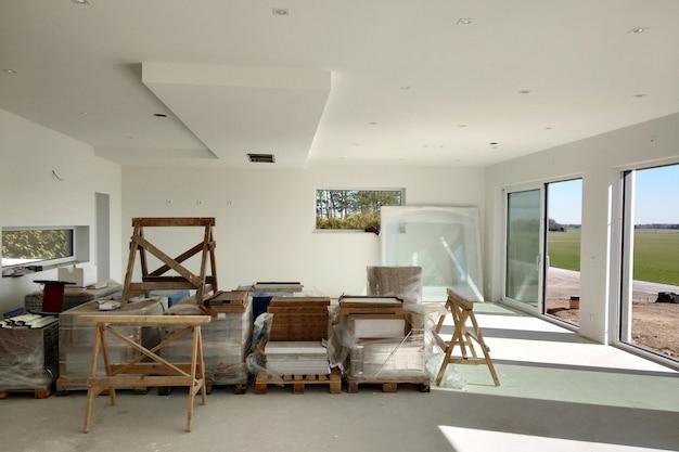 Wnętrze domu z dużym pokojem w trakcie prac remontowych.