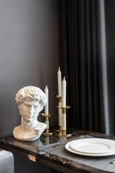 Wnętrze domu ze stołem w jadalni, zastawą stołową ze złotej stali nierdzewnej i sztućcami na marmurowym blacie. projektowanie wnętrz