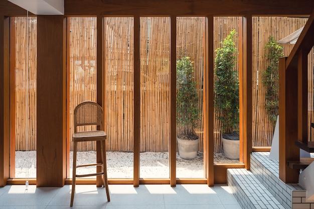 Wnętrze drewnianego szklanego okna z krzesłem splotu i światłem słonecznym w tradycyjnym domu retro