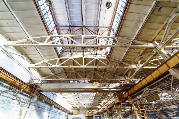 Wnętrze dużego budynku przemysłowego lub fabryki ze stalowymi konstrukcjami. dach wewnątrz nowej dużej i nowoczesnej powierzchni magazynowej.