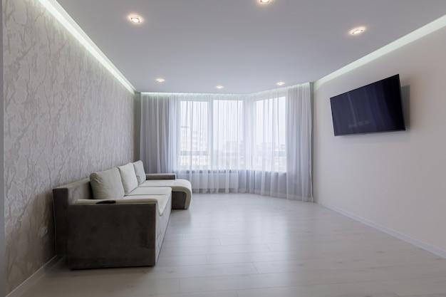 Wnętrze dużego salonu z szarymi ścianami i schodami w nowoczesnym stylu
