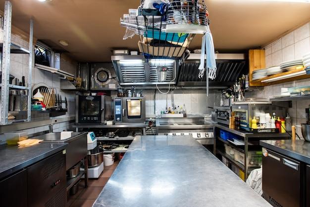 Wnętrze dużej kuchni nowoczesnej luksusowej restauracji, w tym duży długi stół do gotowania, naczynia kuchenne, zlew, półki, kuchenka elektryczna i piekarnik