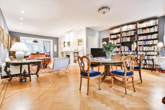 Wnętrze eleganckiej jadalni z wygodnymi krzesłami ustawionymi przy okrągłym stole z kwiatami na półce w domu