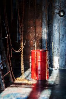 Wnętrze fabrycznego sklepu przemysłowego z łańcuchami i czerwoną beczką oświetlone światłem słonecznym z okna
