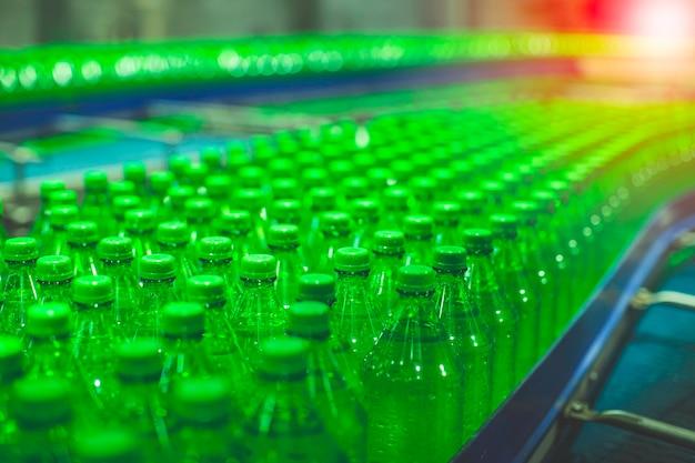Wnętrze fabryki napojów. przenośnik płynący z zielonymi butelkami na wodę.