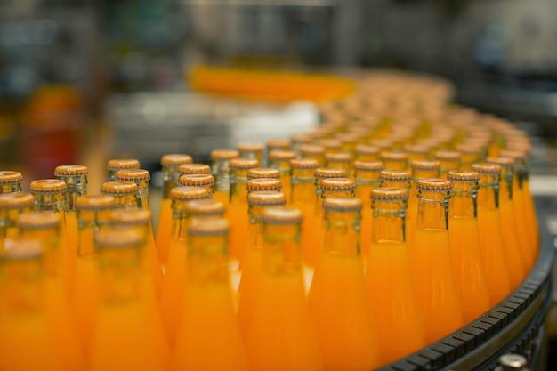 Wnętrze fabryki napojów. przenośnik przepływający z butelkami na sok lub wodę.