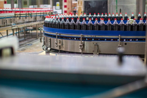 Wnętrze fabryki napojów. przenośnik przepływający z butelkami na wodę gazowaną.