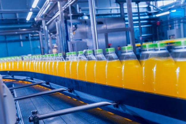 Wnętrze fabryki napojów. przenośnik z butelkami na sok lub wodę. wyposażenie