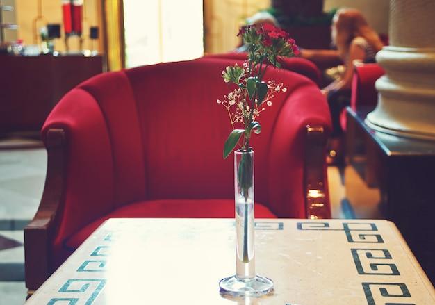 Wnętrze holu hotelu z czerwonym fotelem i stolikiem