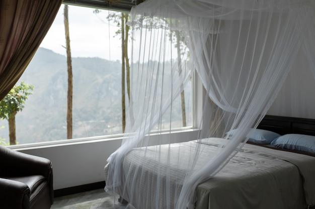 Wnętrze hotelu z dużym panoramicznym oknem i widokiem na górę