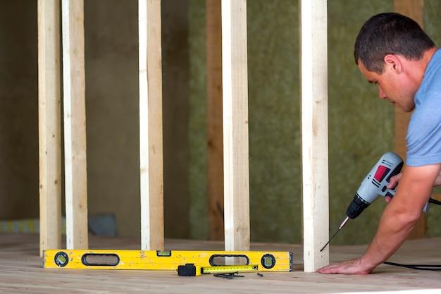 Wnętrze izolowanego poddasza pokoju z dębową podłogą w trakcie przebudowy. młody profesjonalny pracownik używa poziomu i śrubokręta instalując drewnianą ramę do przyszłych ścian. koncepcja remontu i poprawy.