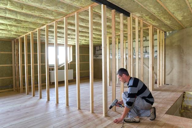 Wnętrze izolowanego poddasza pokoju z rekonstrukcją dębowej podłogi młody profesjonalny pracownik używa poziomu i śrubokręta instalując drewnianą ramę do przyszłych ścian. koncepcja remontu i poprawy.