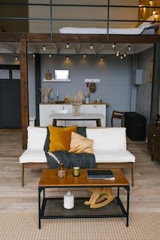 Wnętrze jadalni w stylu skandynawskim, kanapa i stolik kawowy na tle kuchni w szaro-musztardowych kolorach