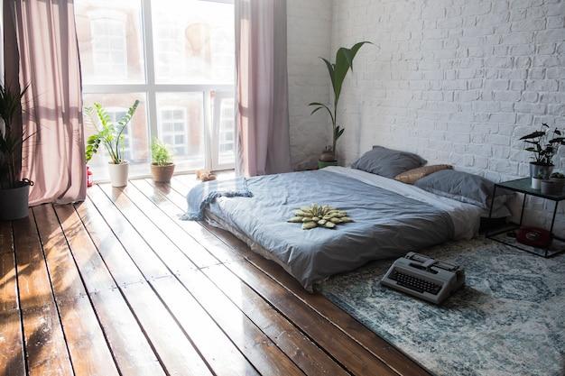 Wnętrze jasne sypialnie z dużymi oknami i mnóstwem roślin doniczkowych
