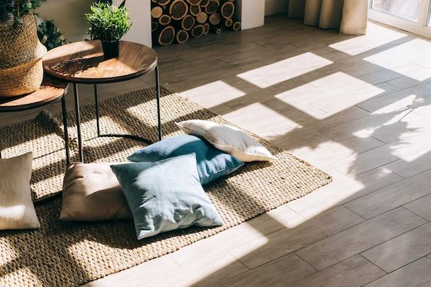 Wnętrze jasnego salonu w stylu skandynawskim ze stolikiem kawowym i poduszkami na podłodze, duży cień z okna na podłogę.