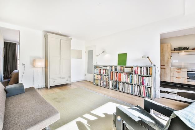 Wnętrze jasnego salonu z regałem i garderobą przy wygodnym siedzisku w nowoczesnym mieszkaniu