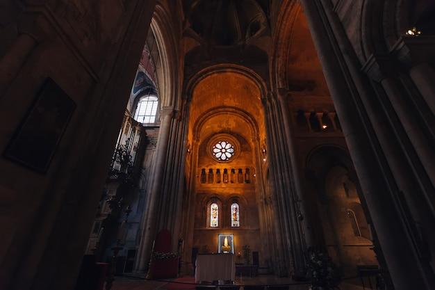 Wnętrze katedry z oknami o różnych kształtach oraz wysokimi łukami i kolumnami