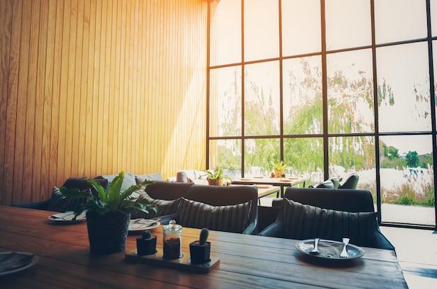 Wnętrze kawiarni z nowoczesną i prostą dekoracją, duże szklane okna. poranne światło