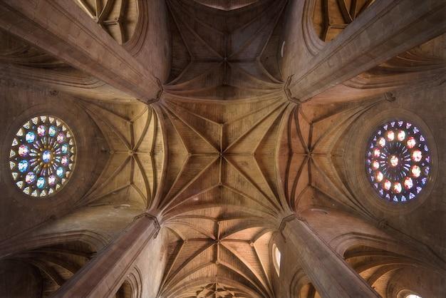 Wnętrze kościoła, święta atmosfera, lekkie promienie przez witraż.