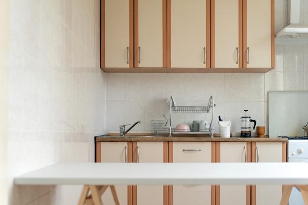Wnętrze kuchni w jasnych pastelowych kolorach. biały stół. nowoczesny projekt kuchni.
