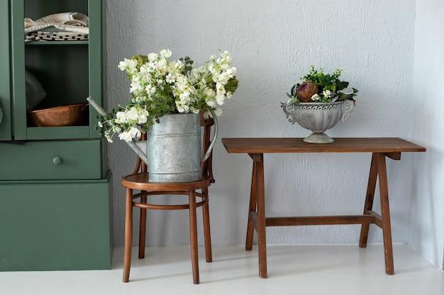 Wnętrze kuchni z meblami piękny bukiet kwiatów w konewce vintage narzędzie ogrodowe