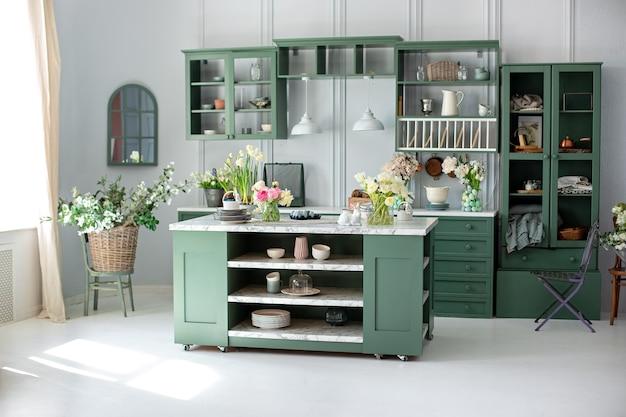 Wnętrze kuchni z meblami w letnim wystroju stylowa kuchnia z kwiatami w wazonie przybory kuchenne naczynia i talerz na stole wyspa kuchenna w jadalni