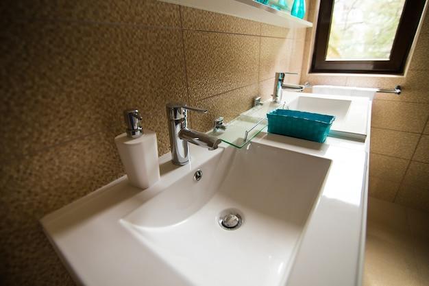 Wnętrze łazienki umywalka bidet toaleta duże lustro ściany są w kolorze jasnobrązowym