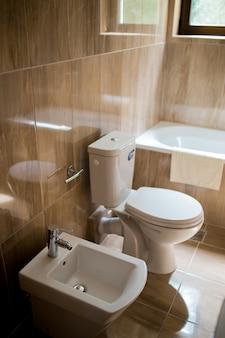 Wnętrze łazienki - umywalka, bidet, wc, duże lustro. ściany są w kolorze jasnobrązowym.