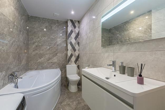 Wnętrze łazienki, w małym eleganckim mieszkaniu, wanna i pralka z toaletą