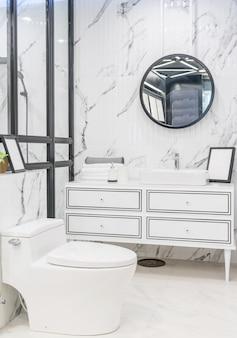Wnętrze łazienki z białą ścianą, zabytkowymi meblami, ręcznikami, toaletą i umywalką