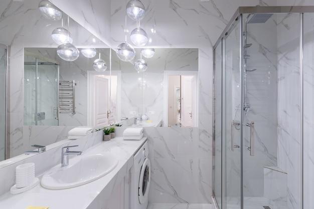 Wnętrze łazienki z białymi marmurowymi kafelkami i nowoczesnym prysznicem