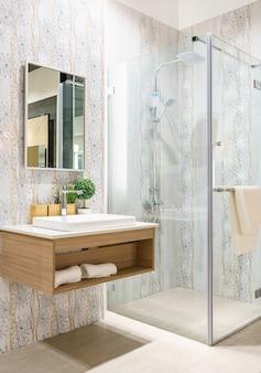 Wnętrze łazienki z białymi ścianami, kabiną prysznicową ze szklaną ścianą i zlewem z kranu