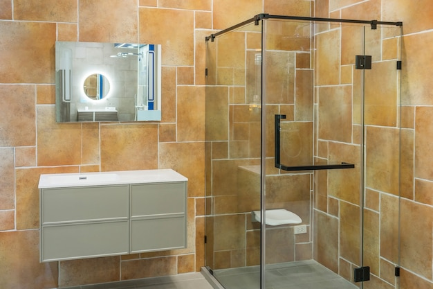 Wnętrze łazienki z białymi ścianami, kabina prysznicowa ze szklaną ścianą